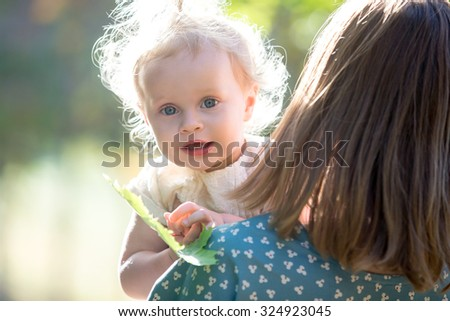 Portrait of happy adorable baby girl with her young mother playing with tree leaf, mom holding her little daughter in arms, walking together in park in warm sunny weather - stock photo
