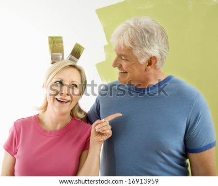 Portrait of happy adult couple standing in front of half-painted wall while man makes bunny ears with paintbrushes behind woman's head. - stock photo