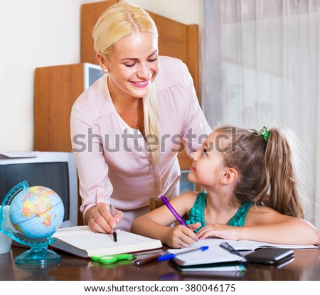 Portrait of happy adult woman and her child having a lesson indoors  - stock photo