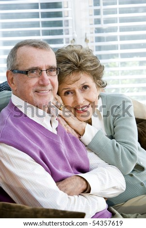 Portrait of happy affectionate senior couple on couch - stock photo