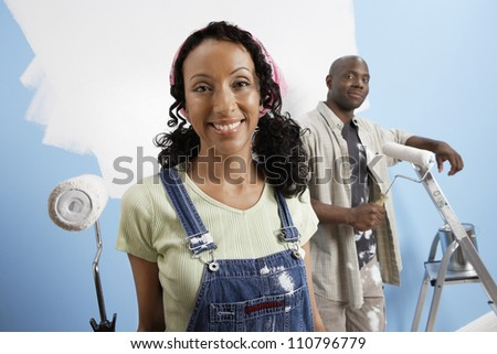 Portrait of happy African American couple painting their new house - stock photo