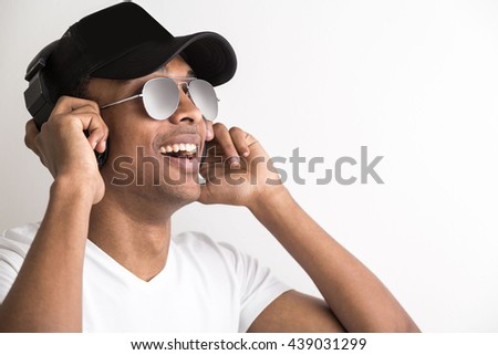 Portrait of happy african american guy in cap and sunglasses listening to music with headphones on light background - stock photo