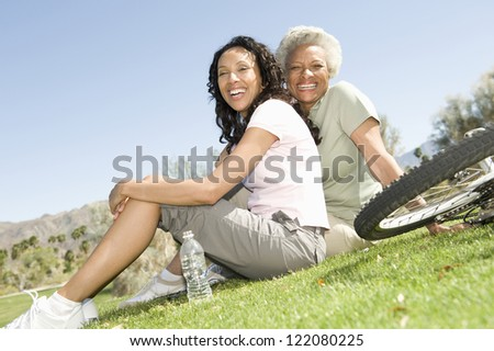 Portrait of happy African American mother and daughter sitting on grass - stock photo