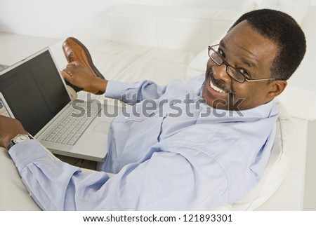 Portrait of happy African American senior man using laptop at home - stock photo