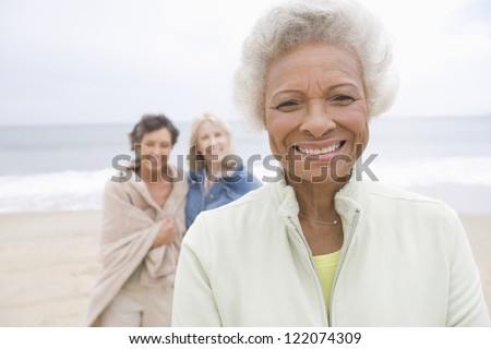 Portrait of happy African American senior woman with friends at beach - stock photo