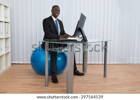 Portrait Of Happy African Businessman Working Sitting On Pilates Ball - stock photo