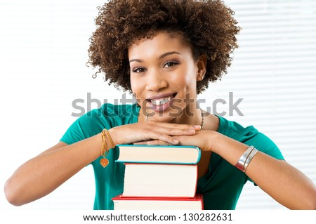 Portrait Of Happy African Student Leaning On Books - stock photo
