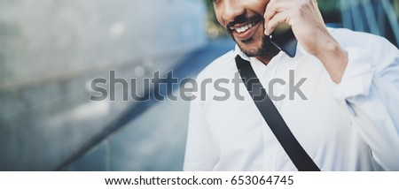 Portrait of happy American African man using smartphone to call friends at sunny street.Concept of happy young people enjoying gadgets outdoors.Blurred background.Horizontal wide,cropped