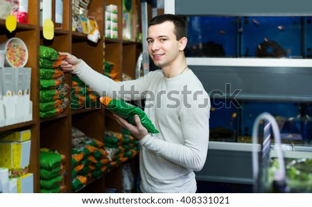 Portrait of happy american guy selecting vet food in petshop
