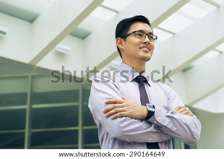 Portrait of happy and confident young asian businessman. The man stands in a street against office buildings and crosses arms looking away - stock photo