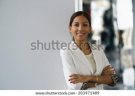 Portrait of happy and self confident latina businesswoman in tailleur, leaning with arms crossed on white wall. Copy space  - stock photo
