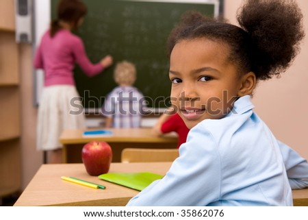 Portrait of happy and smart girl smiling at camera during lesson in classroom
