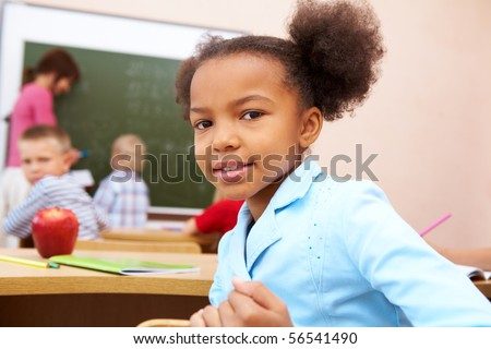 Portrait of happy and smart girl smiling at camera during lesson in classroom - stock photo