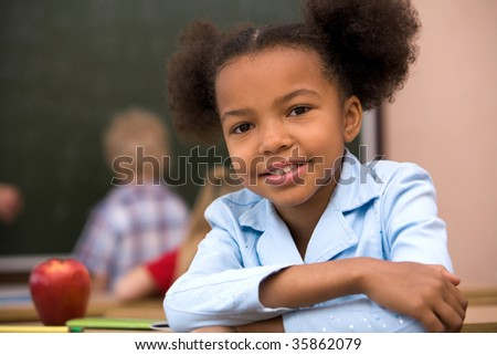 Portrait of happy and smart schoolgirl smiling at camera - stock photo