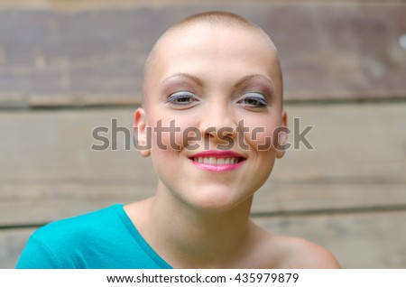 Portrait of happy and young cancer survivor after successful chemotherapy. - stock photo