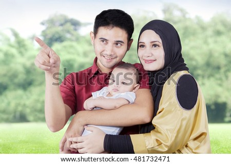 Portrait of happy Arabian parents and their son looking at something at the park