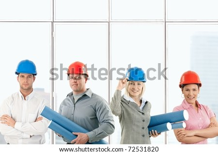 Portrait of happy architect team standing in office, wearing protective hardhat, holding work plan.?