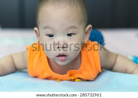 Portrait of happy asian baby on the bed - stock photo