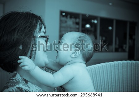 Portrait of happy asian baby with mom on weave bamboo chair, focus on baby - stock photo