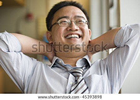 portrait of happy asian business executive; hands behind head - stock photo