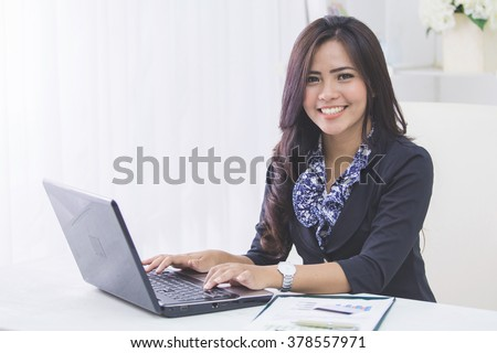 portrait of happy asian business woman using laptop computer while working - stock photo