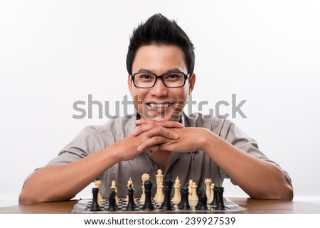 Portrait of happy Asian chess player looking at the camera