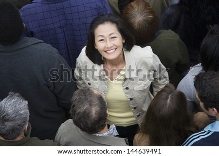 Portrait of happy Asian Chinese woman surrounded by people - stock photo