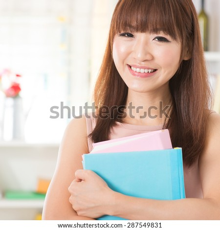 Portrait of happy Asian college girl hands holding books and smiling. Young woman at school library. - stock photo