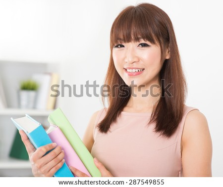 Portrait of happy Asian college girl hands holding books. Young woman at school library.