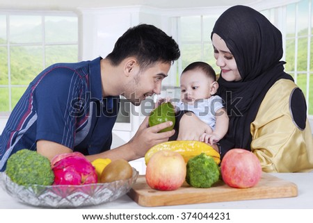 Portrait of happy asian family cooking salad for lunch in the kitchen - stock photo