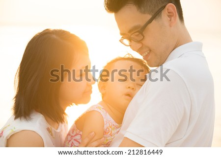 Portrait of happy Asian family outdoor beach vacation, during summer sunset, natural sunlight with flare. - stock photo