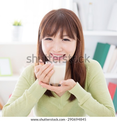 Portrait of happy Asian girl drinking soy milk as breakfast. Young woman indoors living lifestyle at home. - stock photo