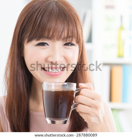 Portrait of happy Asian girl enjoying cup of hot coffee in the morning. Young woman indoors living lifestyle at home.