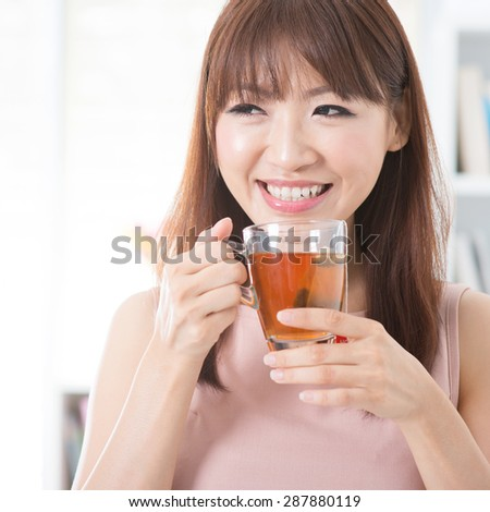 Portrait of happy Asian girl enjoying cup of hot tea in the morning. Young woman indoors living lifestyle at home. - stock photo