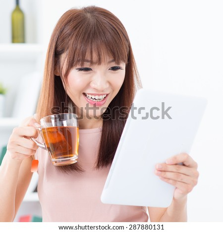 Portrait of happy Asian girl enjoying cup of hot tea while using digital pc tablet in the morning. Young woman indoors living lifestyle at home.