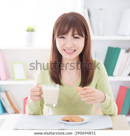 Portrait of happy Asian girl having soymilk and cookies as breakfast. Young woman indoors living lifestyle at home.