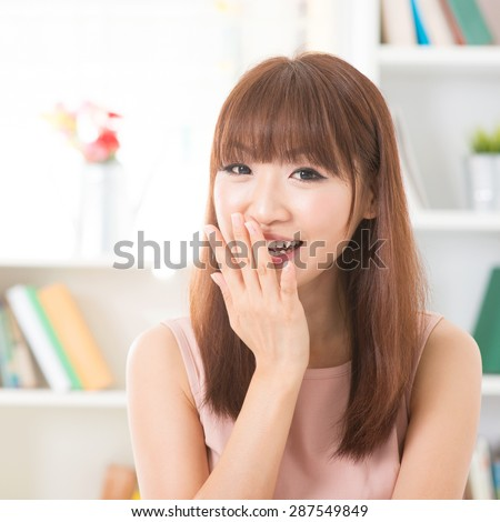 Portrait of happy Asian girl laughing and hand covering mouth. Young woman indoors living lifestyle at home.