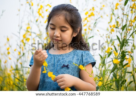 Portrait of happy Asian girl looking flowers on the field, Freedom concept