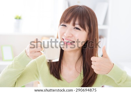 Portrait of happy Asian girl thumb up while drinking milk as breakfast. Young woman indoors living lifestyle at home.