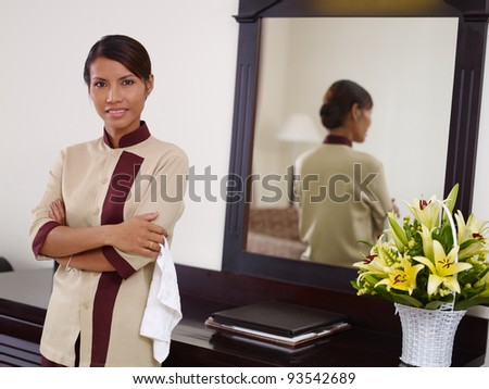 Portrait of happy Asian housekeeper at work in luxury hotel room and smiling at camera