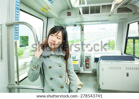 Portrait of happy asian lady holding handhold inside the wagon.Subway commuter woman on Japanese public transport in Tokyo, Japan.