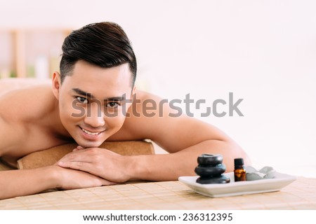 Portrait of happy Asian man in spa salon - stock photo