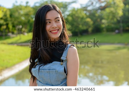 Portrait of happy Asian teenager girl outdoors in park