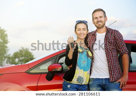 Portrait of happy attractive beautiful couple showingh the keys standing near the red car - stock photo