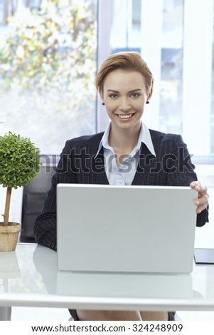 Portrait of happy attractive businesswoman sitting at desk, working with laptop, looking at camera. - stock photo
