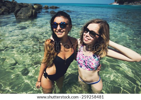 Portrait of happy attractive multiracial female girl friends, smiling and having fun on the beach while having summer vacation on the tropical island - stock photo