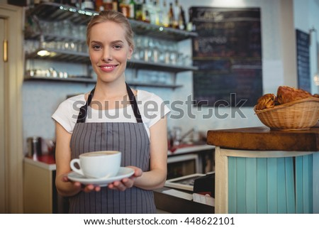 Portrait of happy attractive waitress serving hot beverage at cafe - stock photo