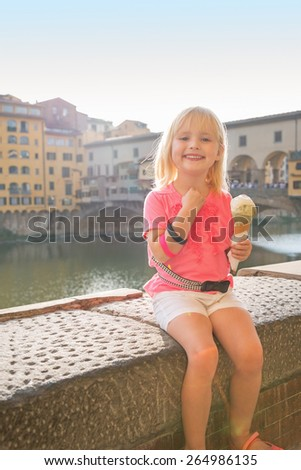 Portrait of happy baby girl eating ice cream near ponte vecchio in florence, italy - stock photo