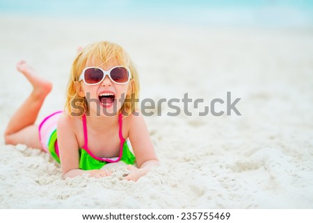 Portrait of happy baby girl in sunglasses laying on beach - stock photo