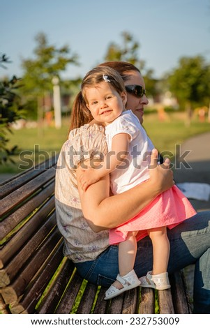 Portrait of happy baby girl standing on park bench hugging to a woman with sunglasses - stock photo